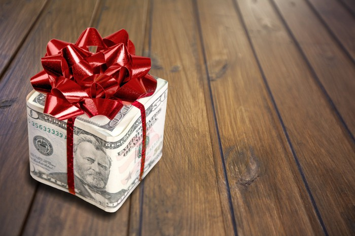 A gift wrapped in cash bills, with a red bow on top.