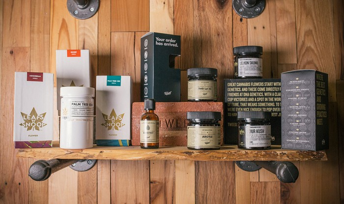Shelf with a dozen cannabis products on a wood-paneled wall.