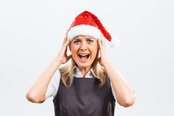 Professionally dressed woman wearing Santa hat holding her head and sporting anguished expression