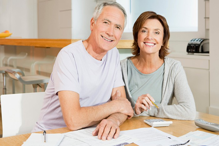 Smiling older man and woman sitting at their kitchen table with documents and calculator.