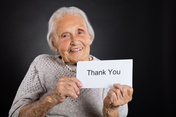 An older woman is smiling and holding a sign that says thank you.