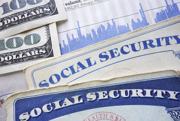 We see two Social Security cards with two hundred-dollar bills next to them.