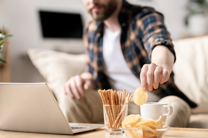 A man eats snacks while working at his computer.
