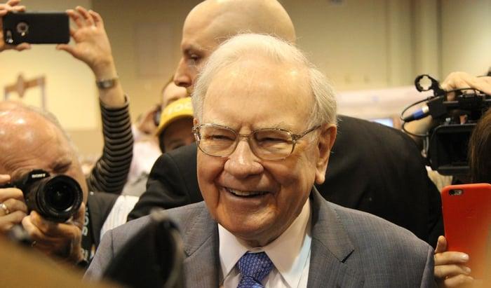 Warren Buffett smiles surrounded by reporters.