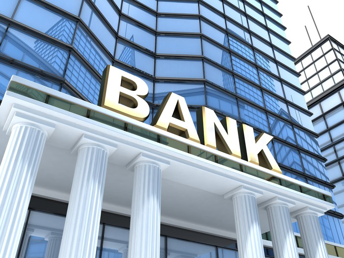 White columns in front of a glass building with a sign that says bank.
