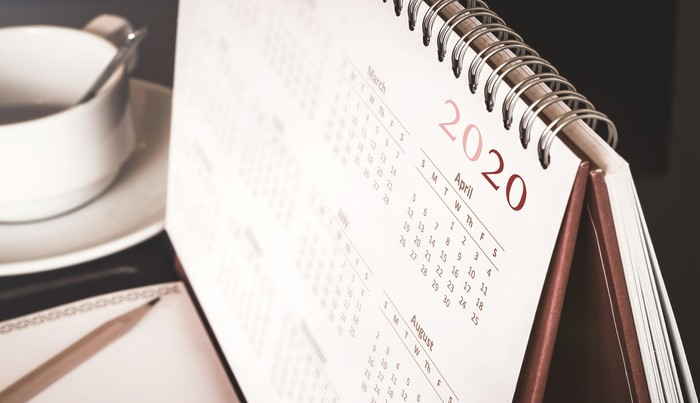 2020 calendar sitting next to notebook and mug