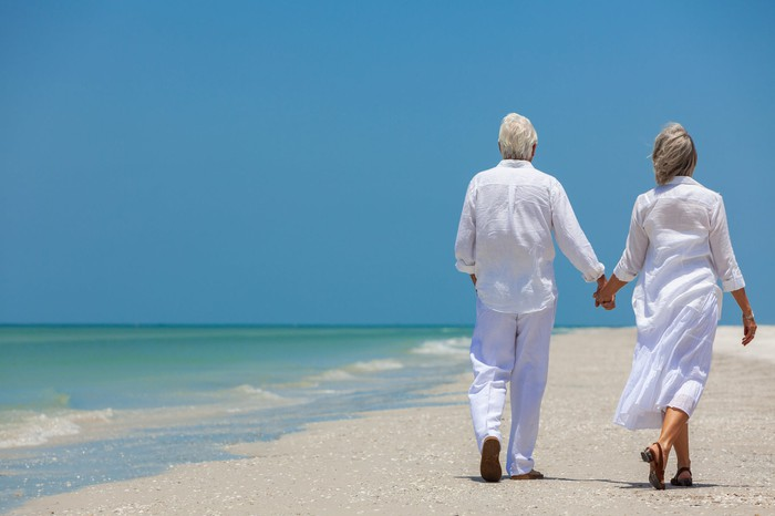 Senior couple walking on a deserted beach on a bright, sunny day.