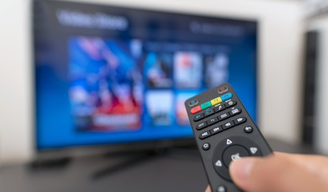 Man holding a remote pointed at blurred out television streaming video