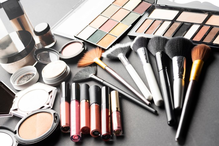 Multiple cosmetic products like makeup and brushes laid out on a flat surface.