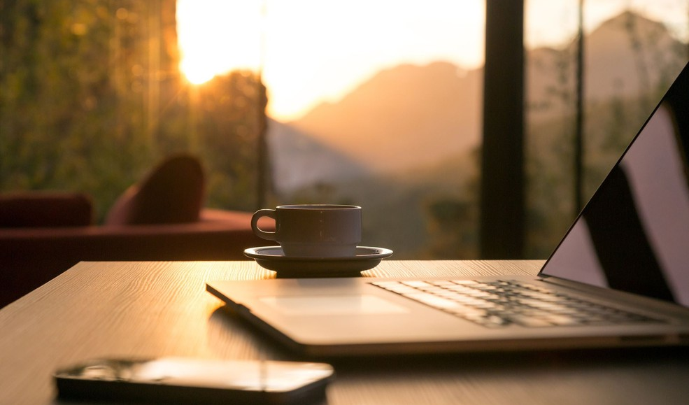 laptop computer coffee mug and phone sitting on desk with sunrise in background morning (1)
