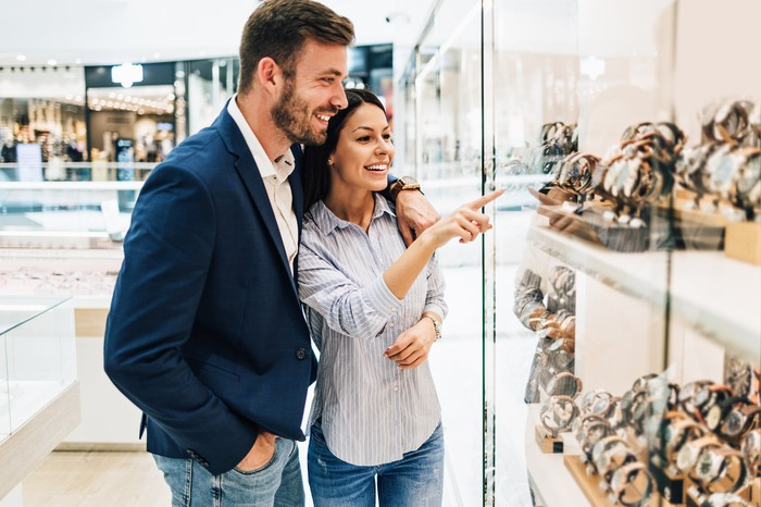 A man and woman in a jewelry store looking at a case of watches.