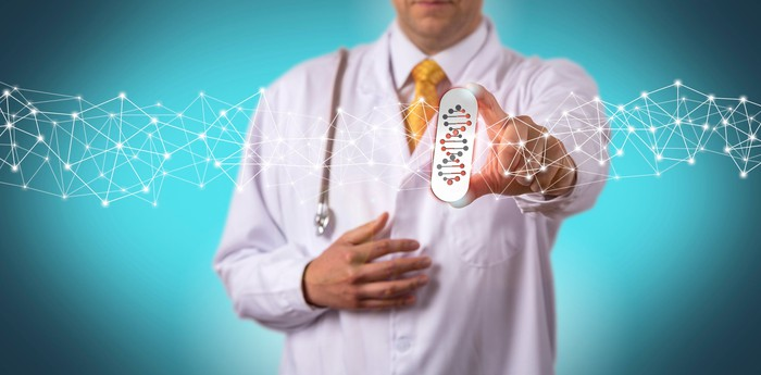 A male doctor holding a big pill with a DNA image on it.