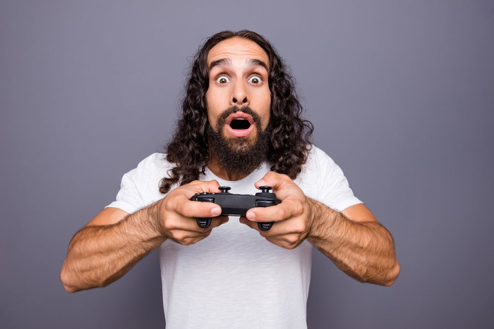 A man with long hair holds a gaming controller and is surprised facing into the camera.