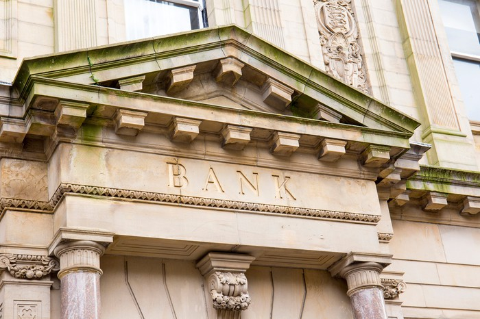 "The stone exterior of a bank branch with the word ""bank"" engraved over the door."