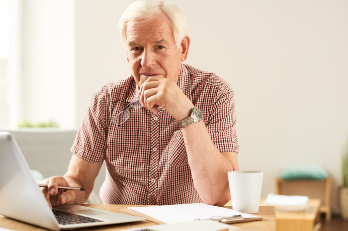 Older man with serious expression at a laptop