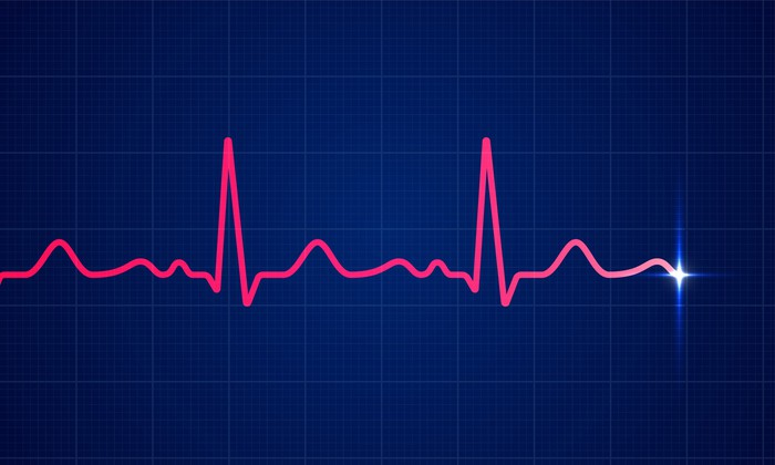 A heartbeat displayed as a pink electrocardiogram rhythm on a blue background.