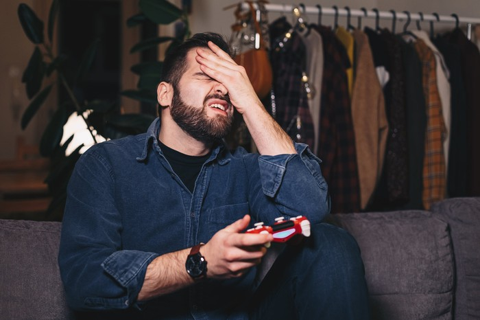 Man cringing while  playing video game