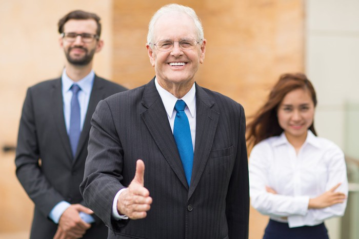 Older man in a suit giving a thumbs up.