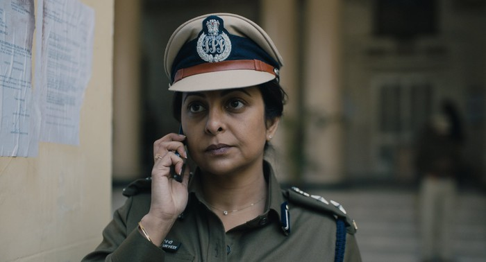 A female police officer in India speaking on a cell phone.