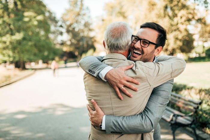 Older man and younger man embracing