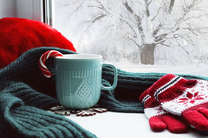 Winter scene through a window, with snow outside, and gloves, scarf, and mug of cocoa on the windowsill