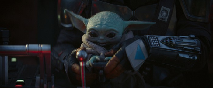 The Child sitting in The Mandalorian's lap