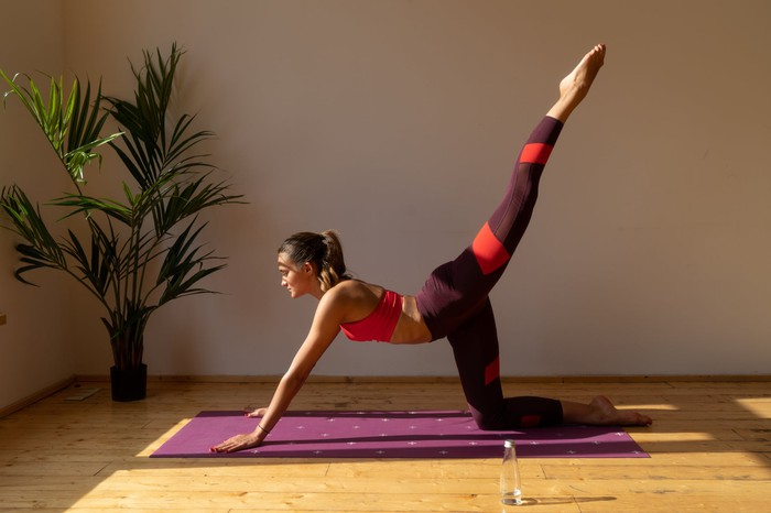 A woman in yoga clothing has both hands and a knee on a purple mat, as she stretches one leg upward.