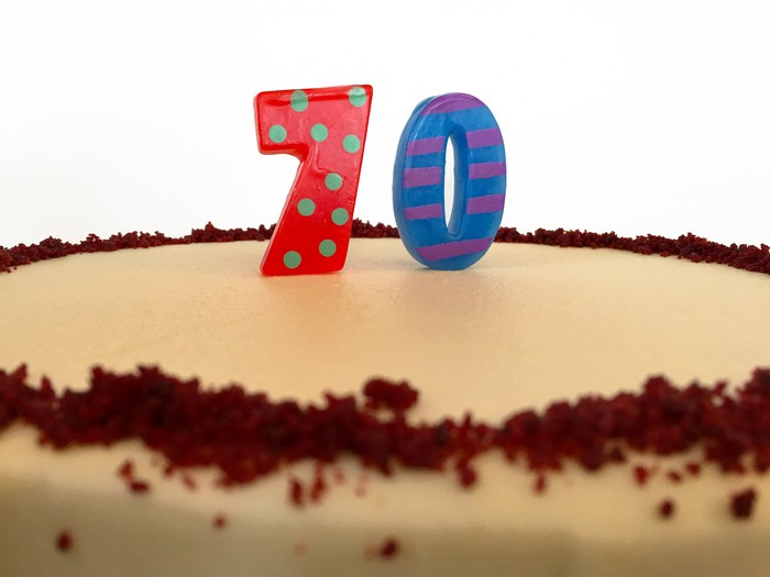 Cake with candles in the shape of the number 70 on top