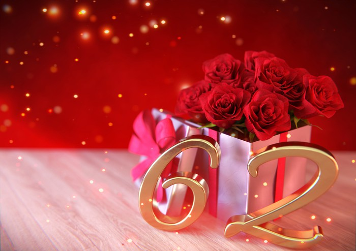 The number 62 in gold in front of a gift box of roses