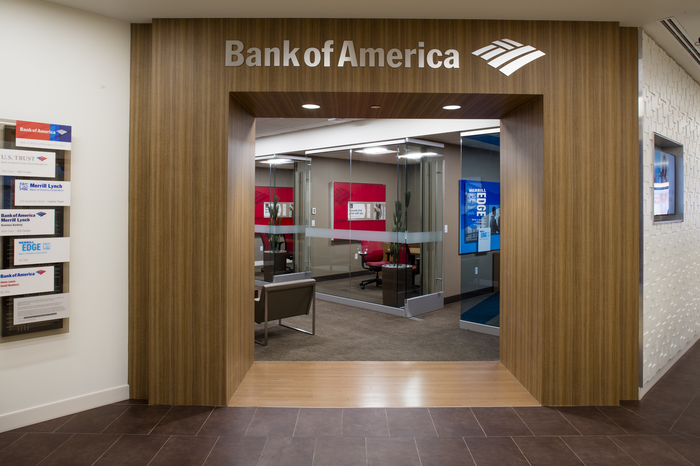 Wood archway with Bank of America logo, leading into bank through glass doors.