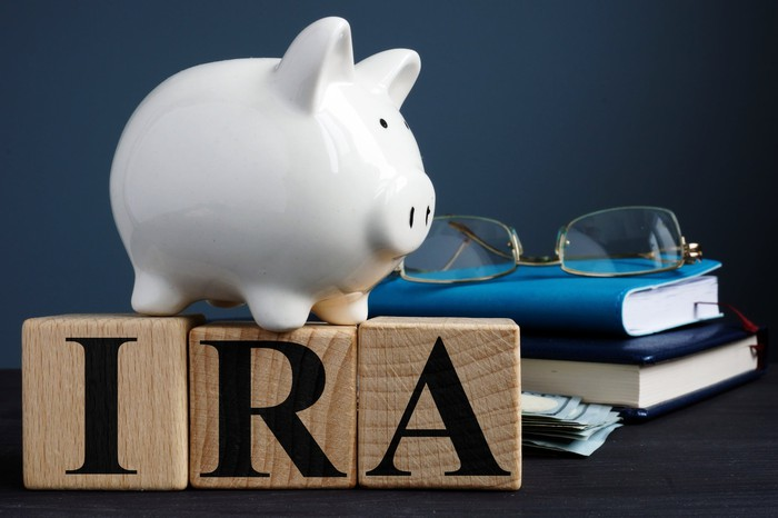 Piggy bank standing on IRA letters with glasses and books in background