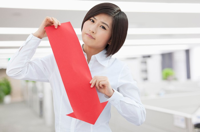 A young woman with a frown on her face holds a red arrow made of paper pointing downward.