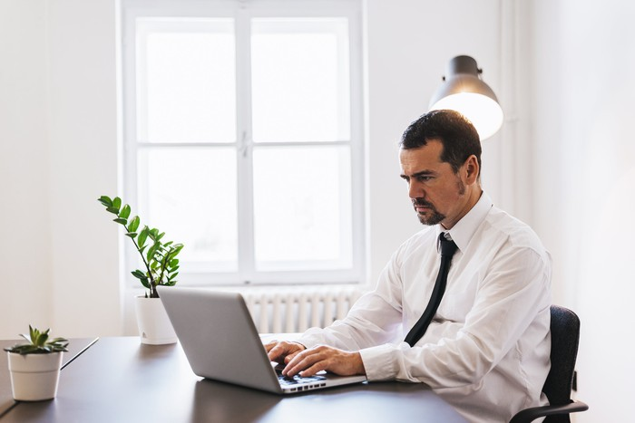 Professionally dressed man at laptop with serious expression