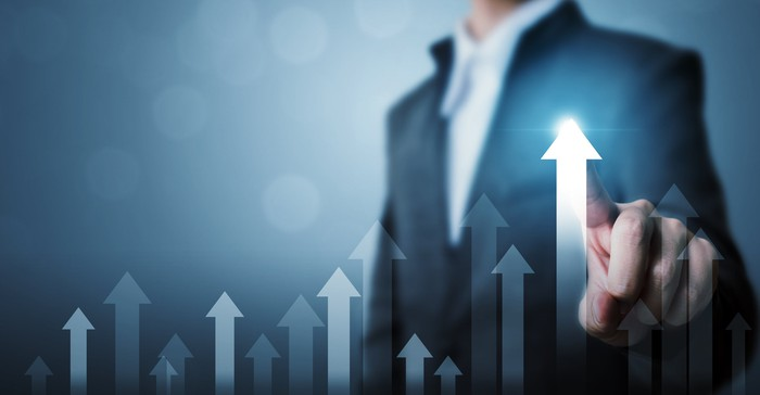 A businessman points to a rising arrow on a chart.