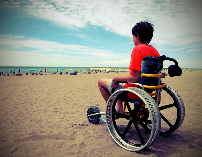 A young boy in a wheelchair that's on a sandy beach.