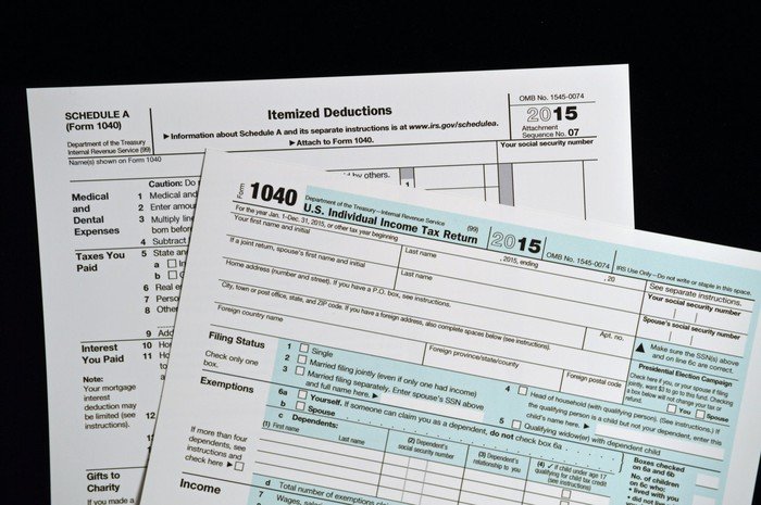 Tax Form 1040 with Schedule A behind it
