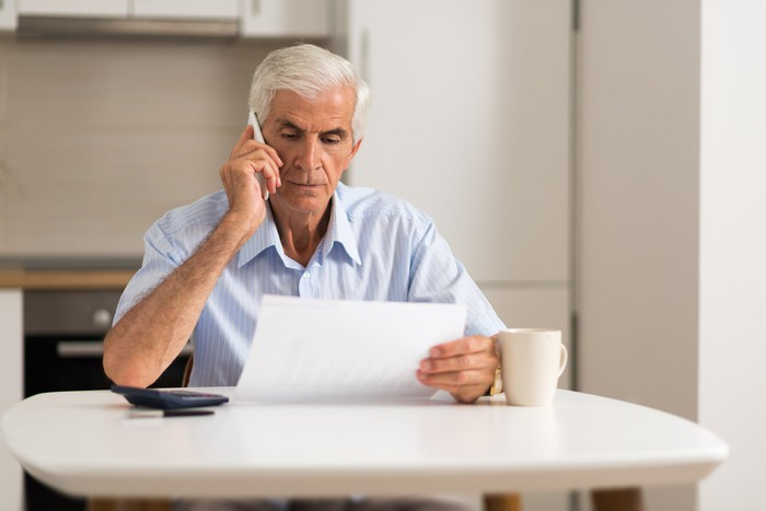 Senior man with serious expression holding document while talking on phone in his kitchen.