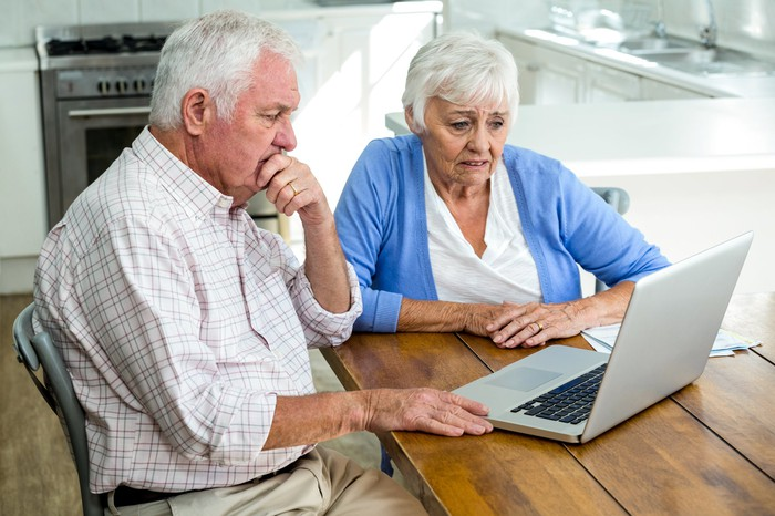 Older man and woman sitting at laptop, sporting concerned expressions