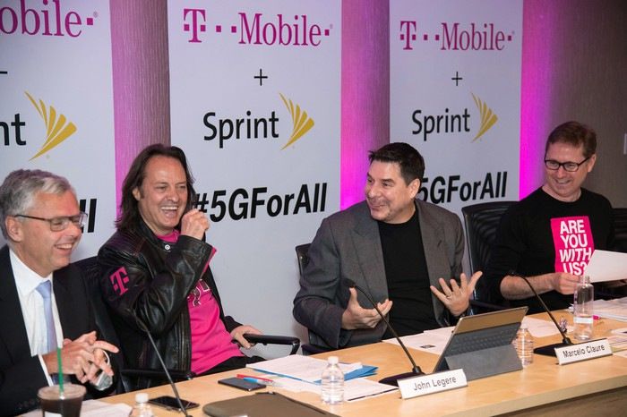 John Legere and Marcelo Claure sitting behind a table and laughing