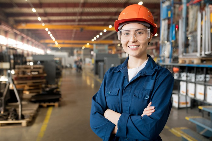 A female technician in a hard hat smiles into the camera inside a modern factory.