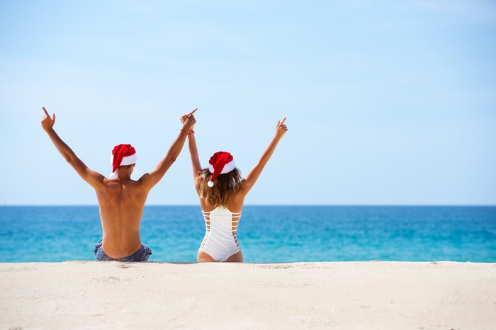 2 people in Santa hats on a beach.