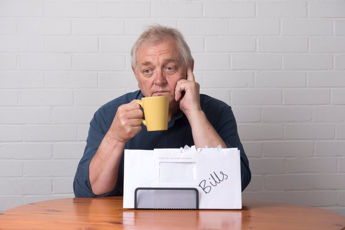 A visibly worried senior man holding up a coffee mug with a pile of bills on the table in front of him.