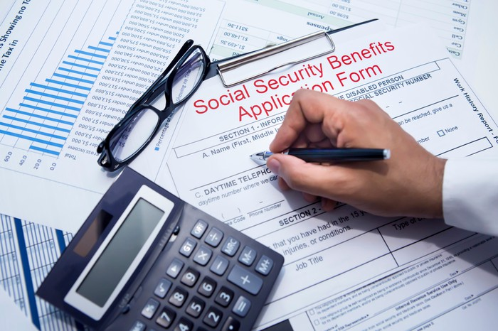 A hand filling out a Social Security benefits application form, with a calculator and pair of eyeglasses on top of it.