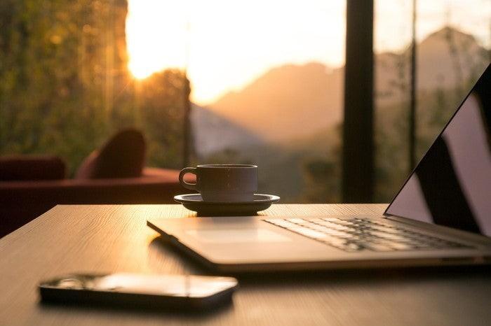 A laptop, phone, and cup of coffee sit on a desk next to a window revealing a view of the sun and mountains.