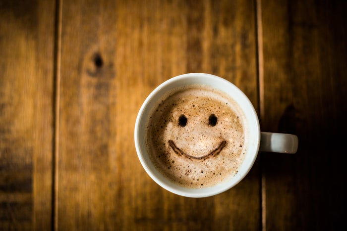 A coffee mug with a smiley face made from coffee and frothy milk