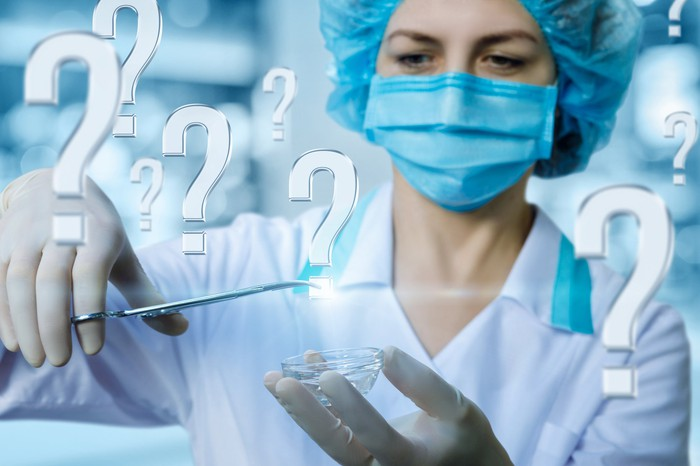 Doctor surrounded by question marks and grabbing a question mark with her clamp.
