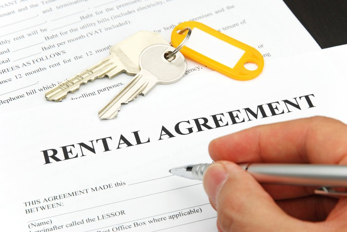 A right hand signing a rental agreement, with a set of keys on top of it.