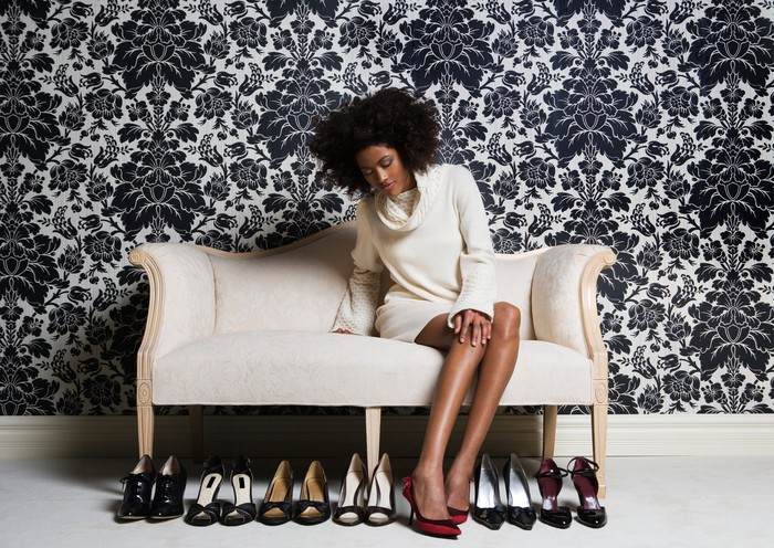 A woman sitting on a couch with numerous pairs of shoes at her feet