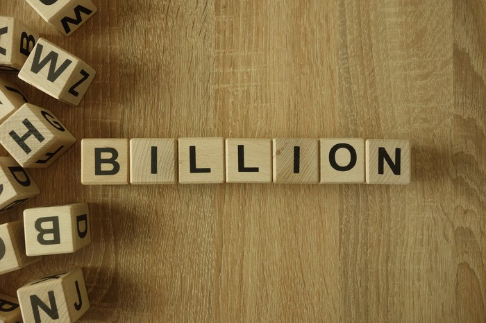 "Wooden blocks that spell out the word ""billion"" arranged on a wooden table top."