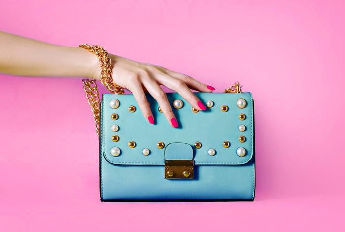 Woman's hand on a handbag.